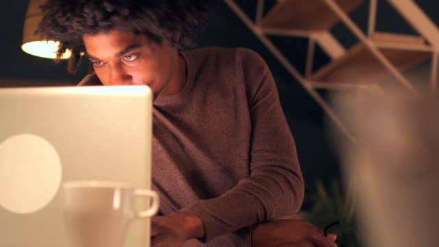 vídeos de stock, filmes e b-roll de trabalhando de casa em um laptop tarde da noite. - one young man only