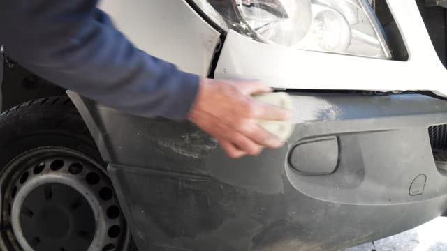 Working in a car service, close up, repairing front bumper of a car, professional occupation, safety at work,