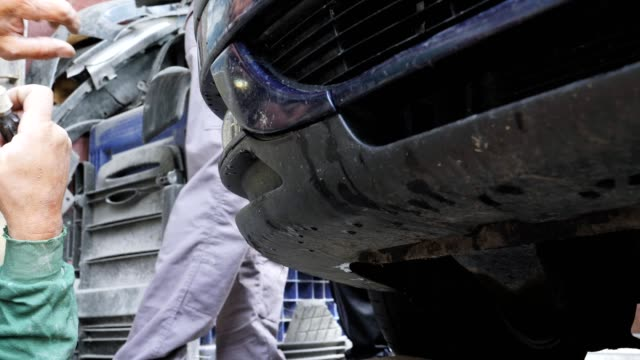 working in a car service, close up, repairing front bumper of a car, professional occupation, safety at work, - job listing stock videos and b-roll footage