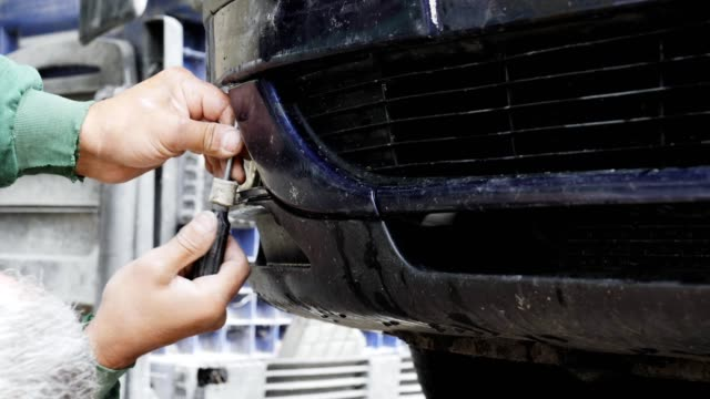 working in a car service, close up, repairing front bumper of a car, professional occupation, safety at work, - bumper car stock videos & royalty-free footage