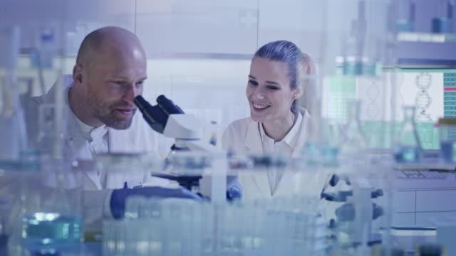 現代のラボラトリーで働く。研究中の女性と男性の冗談 - 顕微鏡点の映像素材/bロール