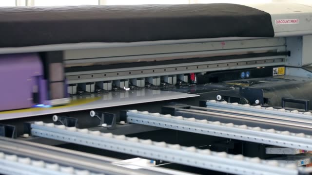 Working industrial large format UV printer for printing on big plastic panel. Printer machine inkjet during production.