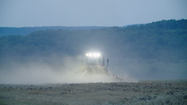 working late. turn on the headlights while plowing an agricultural field. tractor working at the oilseed rape field at the end of the harvest season plowing the soil at night with headlights on. agricultural occupation. - agricultural occupation stock videos & royalty-free footage