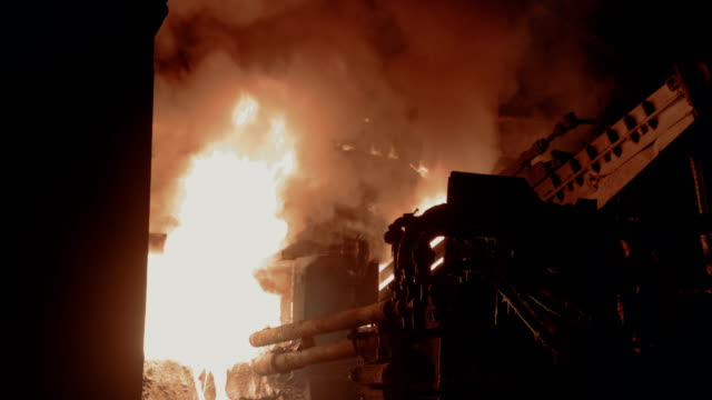 Working machines near blast furnace at steel mill