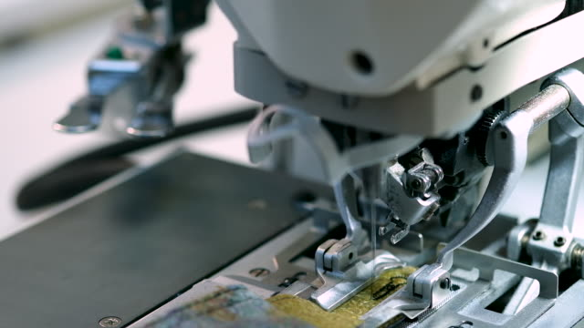 working macro detail of the sewing machine. the needle moves and sews the fabric. the cutting of the material at a textile factory - needle plant part stock videos & royalty-free footage