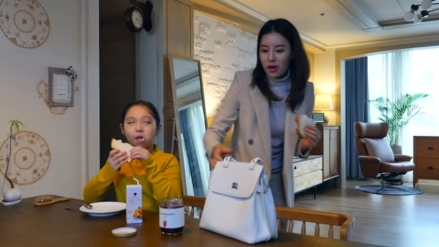 working mom - daughter eating breakfast and mother combing daughter's hair at dining table before commuting - working mother stock videos & royalty-free footage