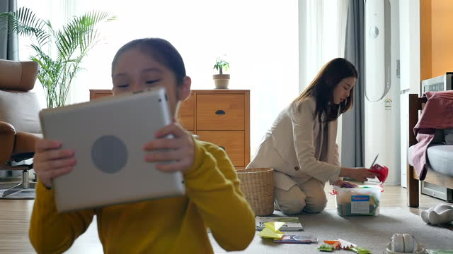working mom - mother coming back from work and arranging living room while daughter playing delightfully with tablet pc - ため息点の映像素材/bロール