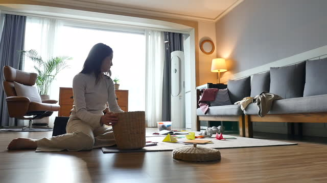 working mom - mother coming back from work and arranging messed living room - ため息点の映像素材/bロール