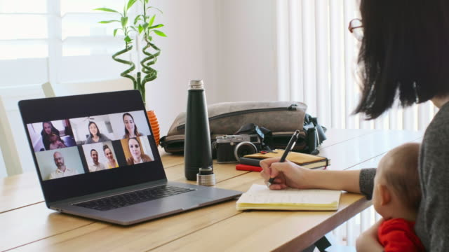 working mother at home on a web chat meeting - working from home stock videos & royalty-free footage
