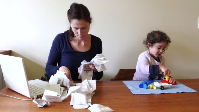 vidéos et rushes de working mother does accounting with baby toddler - limite