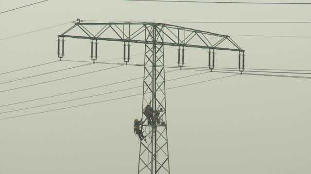 working on a high-voltage pylon - high voltage stock videos & royalty-free footage