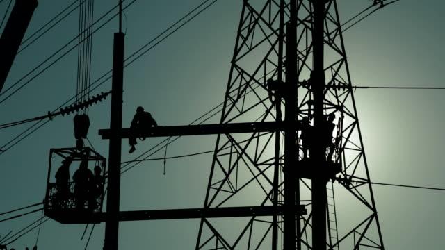 arbeiten auf high voltage pole. - hochspannungsmast stock-videos und b-roll-filmmaterial
