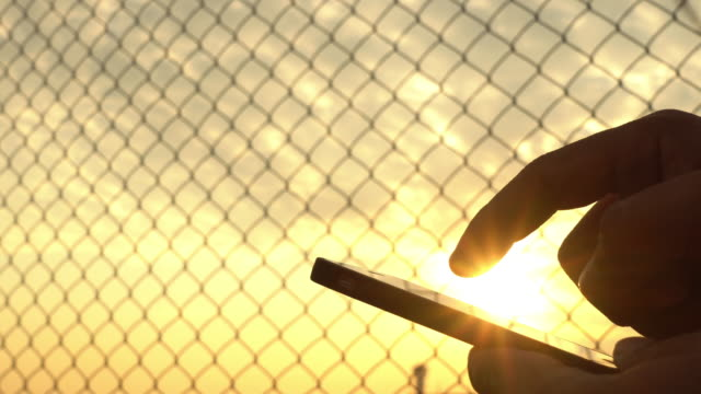 close up: working on smartphone at sunset - chainlink fence stock videos and b-roll footage