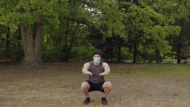 vídeos de stock e filmes b-roll de working out in the park during social distancing - treinar