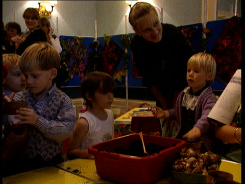 Childcare ENGLAND London CMS Woman working in Playgroup with number of small children CMS Small boy in group CMS Child's hand takes glue from pot and...
