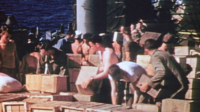 vidéos et rushes de working party of us navy sailors lifting crates and carrying them below on the deck of a ship during world war ii - marin