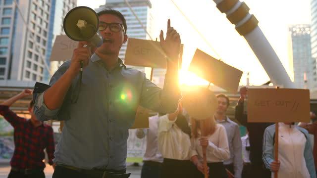 arbeitende menschen protestieren, um etwas zu fordern mit einem führer, der ein megaphon vor sich hält. - demokratie stock-videos und b-roll-filmmaterial