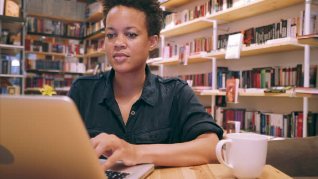 vídeos de stock, filmes e b-roll de trabalhando remotamente em uma livraria. - solução