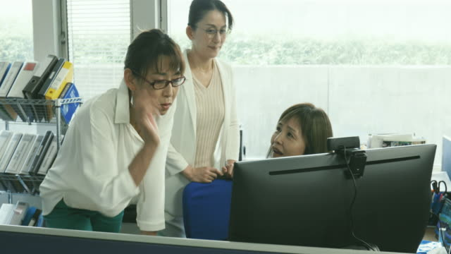 working senior business woman is talking to colleague during informal meeting in front of monitor at office - プレゼン点の映像素材/bロール