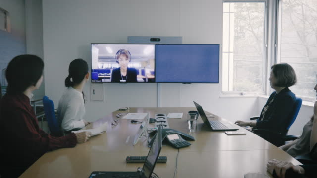 stockvideo's en b-roll-footage met working senior business woman is talking to colleague during meeting in office meeting room by tv conference - conferentie