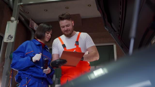 vídeos y material grabado en eventos de stock de trabajar juntos en un taller de reparación de automóviles - aprendiz
