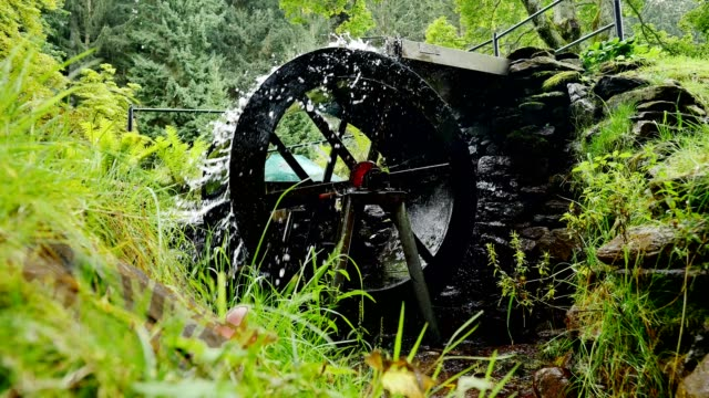 working water wheel driving generator on mountain stream - water wheel stock videos and b-roll footage