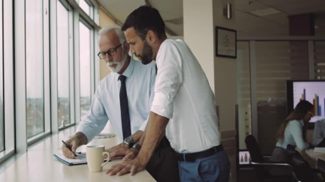 zusammenarbeit mit erfahrenen manager im büro - leitende position stock-videos und b-roll-filmmaterial
