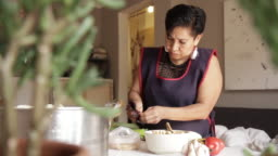 Working-Class mother cooking tamales with mole negro at home