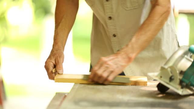 Workman carpenter cutting board with skill saw.