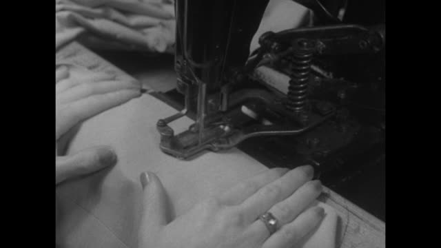 stockvideo's en b-roll-footage met workman cutting rayon fabric / three shots of women sewing rayon fabric with sewing machines / woman checking dress made of printed rayon placed on... - zoom out