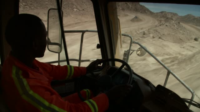 a workman drives a construction vehicle down a quarry road. available in hd. - dump truck stock videos and b-roll footage