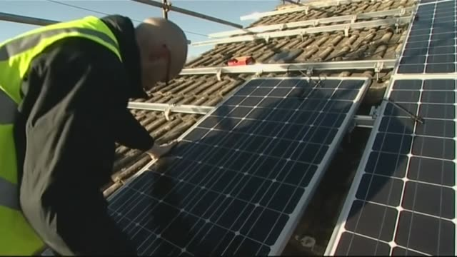 workman fitting solar panels to roof of house - solar panels stock videos & royalty-free footage