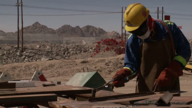 a workman in a mask and safety gloves welds a piece of metal. available in hd. - 石切場点の映像素材/bロール