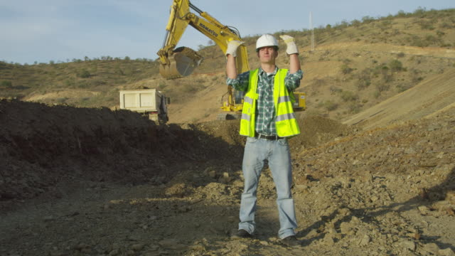 WS workman in high-visibility vest acting as banksman to camera, guiding imaginary vehicle to a stop; earth moving equipment operating in background