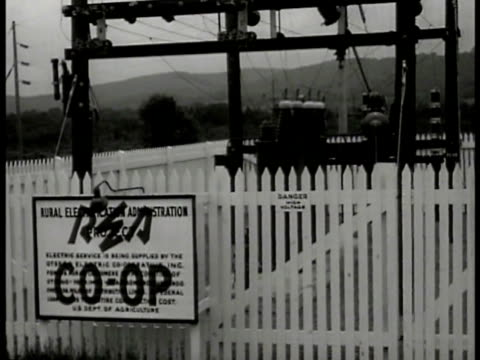 Workman stringing electric wire on farm telephone pole WS Transformer w/ REA Coop sign DEDICATION SOT Farmer speaking to other farmers about...