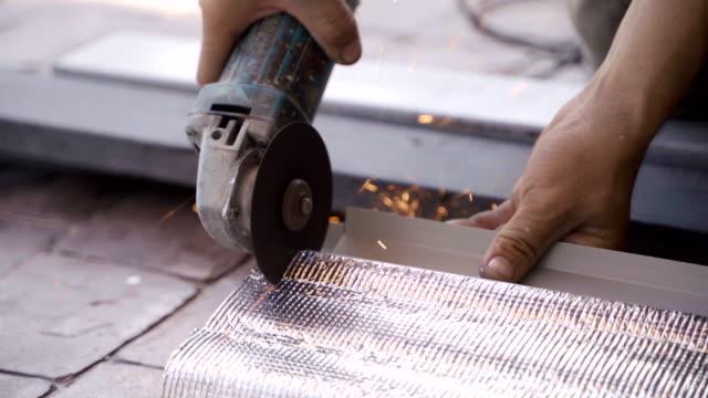 vídeos de stock, filmes e b-roll de operário usa máquina de moagem portátil para cortar e fazer o telhado. - serra circular