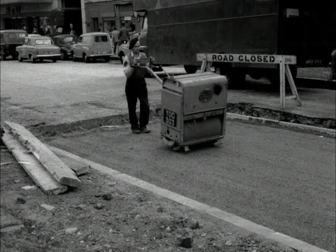 workman uses a hand held roller to flatten a section of newly prepared road. - 1950 1959 stock videos & royalty-free footage
