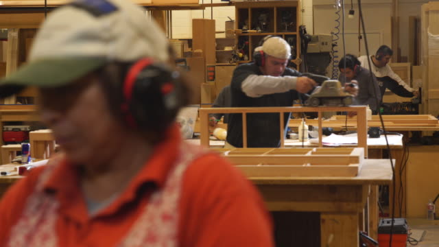 workman uses belt sander to finish custom windows in busy woodwork shop - ohrenschützer stock-videos und b-roll-filmmaterial