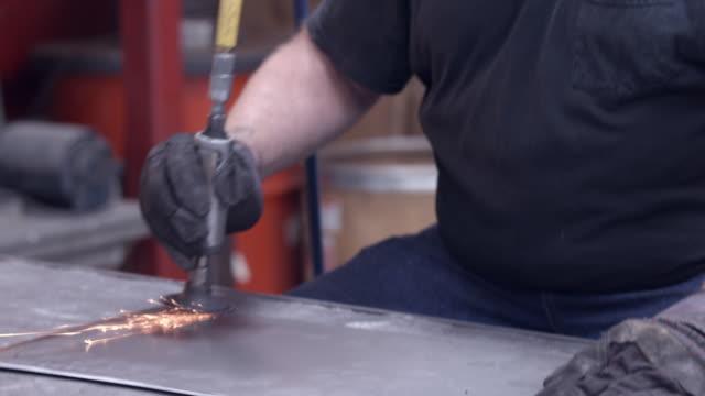 workman using disc grinder power tool to smooth sharp edges of plasma cut work piece from sheet metal / Redlands, California, USA