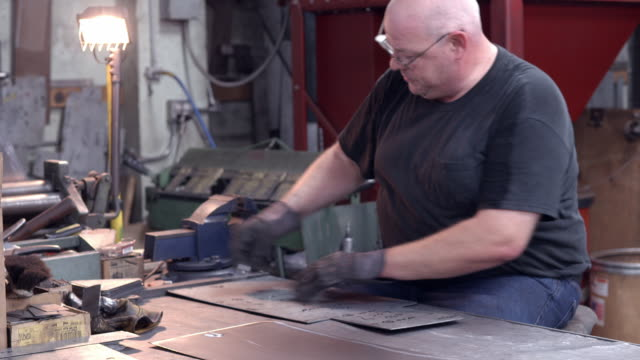 workman wearing protective gloves punches out precut holes in piece of sheet metal / redlands, california, usa - protective sheet stock videos and b-roll footage