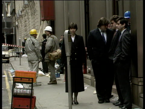 workmen clear glass from shattered windows beside baltic exchange building following ira bomb attack as office workers wait behind cordons 13 apr 92 - rettungsdienst mitarbeiter stock-videos und b-roll-filmmaterial