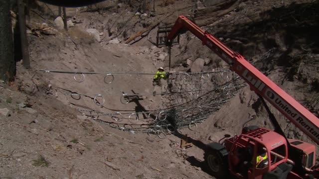 workmen install wire fence in canyon near santa clara pueblo - プエブロ文化点の映像素材/bロール