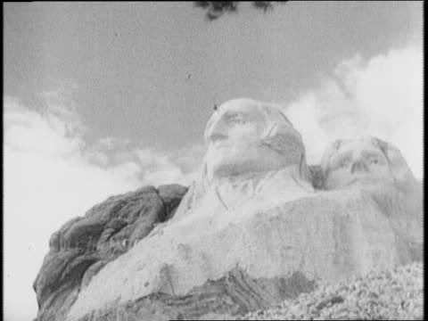 workmen leave with lunchboxes dismantle machinery / lincoln borglum stands before models of faces / borglum adjusts bust of roosevelt sitting next to... - badlands national park stock videos & royalty-free footage