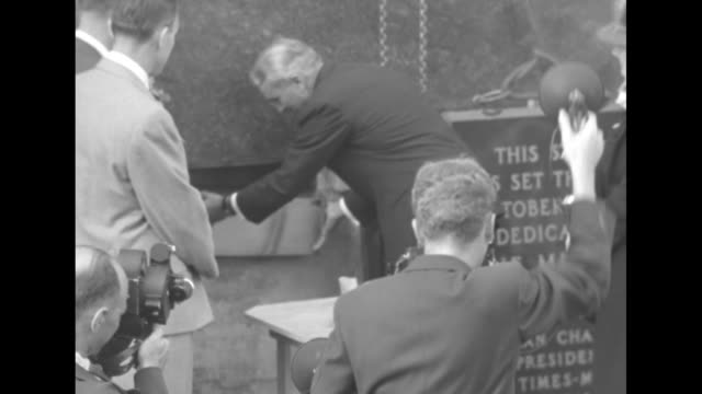 Workmen setting plaque next to place for cornerstone of building crowd watching / Norman Chandler publisher of 'The Los Angeles Times' and president...