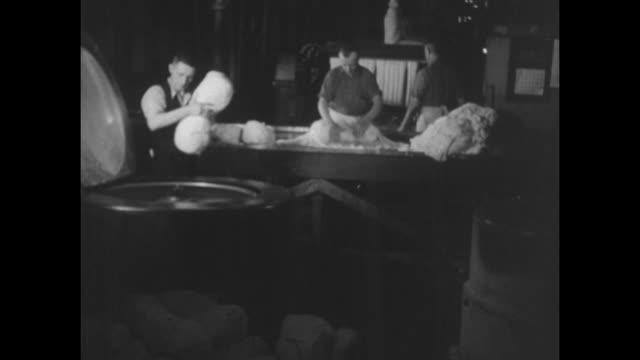 vidéos et rushes de workmen taking tubes of cellulose converted into rayon out of machine and placing them on trays / two shots of women wrapping tubes of rayon with... - actualités cinématographiques