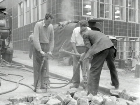 workmen use pneumatic drills to break up a road 1955 - bauarbeiter stock-videos und b-roll-filmmaterial