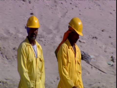 workmen walk across sand dunes in yellow overalls dubai - erezione video stock e b–roll