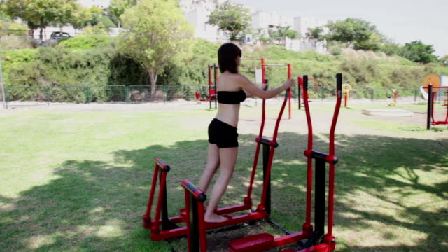 workout for legs  on outdoor elliptical cross trainer. - cross trainer stock videos and b-roll footage