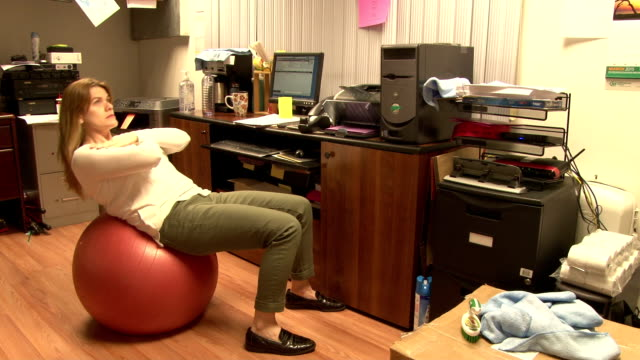 workplace exercise - woman working out in her office - pallone per fitness video stock e b–roll