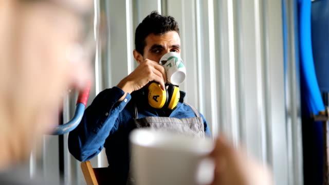 vídeos de stock e filmes b-roll de workshop workers having coffee break - fazer uma pausa